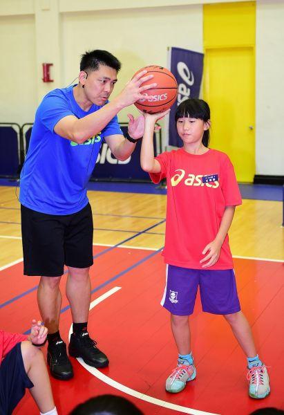 總教練羅興樑貼身指導小球員投籃姿勢,成為頂尖小射手。(大漢集團提供)