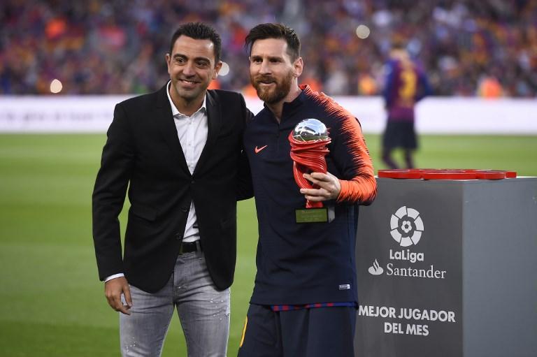 梅西(右)從前隊友哈威手中接過巴薩單月最佳球員獎。法新社