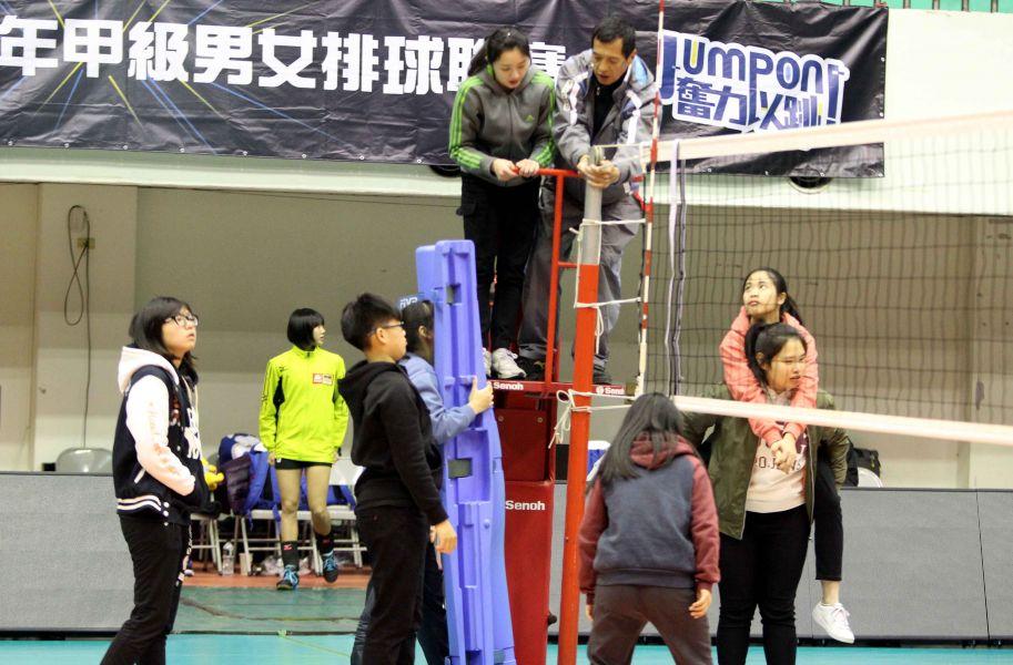 嘉義高商排球隊同學們在中華排協場地組彭文龍(上右)指導下架設球網。林嘉欣/攝影。