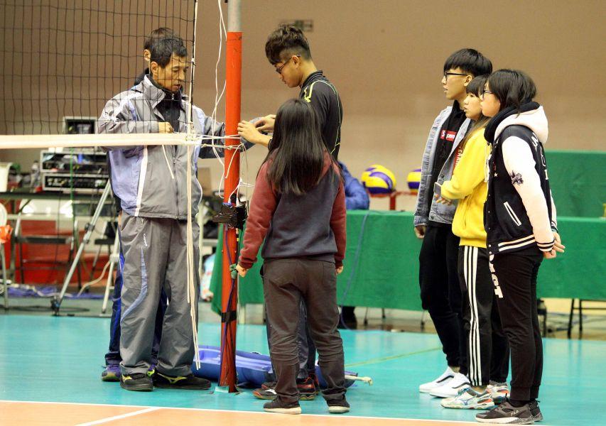 嘉義高商排球隊在中華排協場地組彭文龍(左)指導下架設球網。林嘉欣/攝影