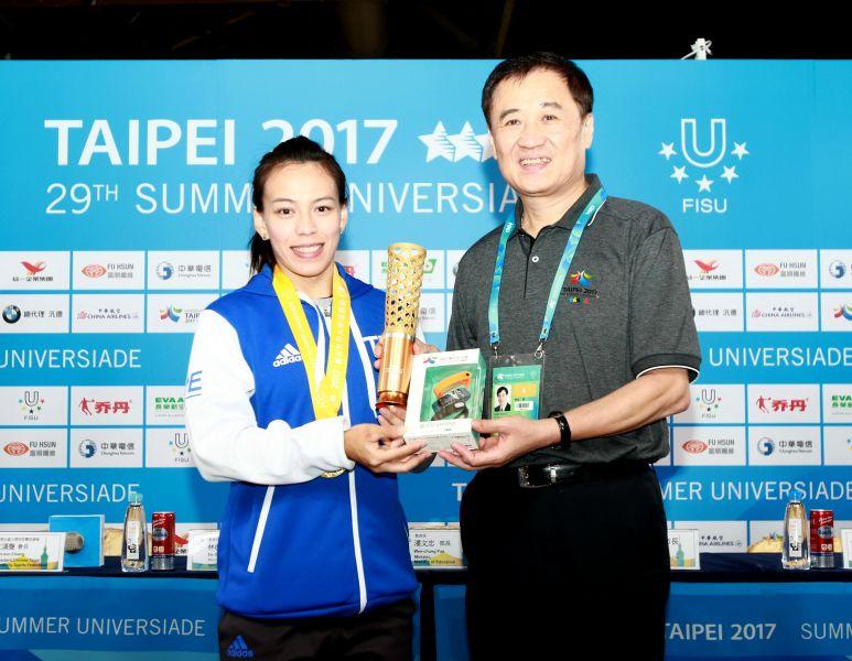 北市副市長陳景峻(右)頒贈世大運紀念品給舉重金牌國手郭婞淳(左)。台北世大運組委會提供