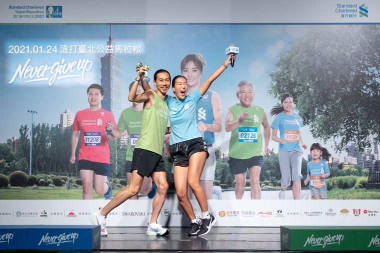 2021渣打臺北公益馬拉松超級戰隊隊長張嘉哲與時尚戰隊隊長莫莉,拿著施華洛世奇獎牌,現場示範完賽時尚照。大會提供