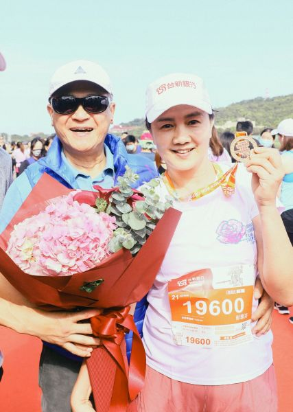 台新金控董事長吳東亮在終點獻上鮮花,熱情迎接成功征服21公里的夫人彭雪芬。路跑協會提供