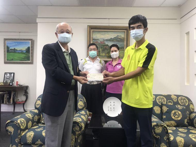 台灣高爾夫俱樂部會長紀文豪(左)以個人名義提供300萬元無息貸款給球場全體桿弟,由桿弟代表謝志偉接受。後左為桿弟管理組長王聲起丶後右為副理呂麗還。官方提供
