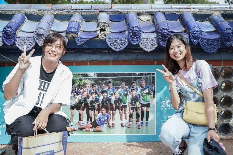 温以勤(左)、陳昱潔(右)在永信杯冠軍牆和去年奪冠照片合影。大會提供