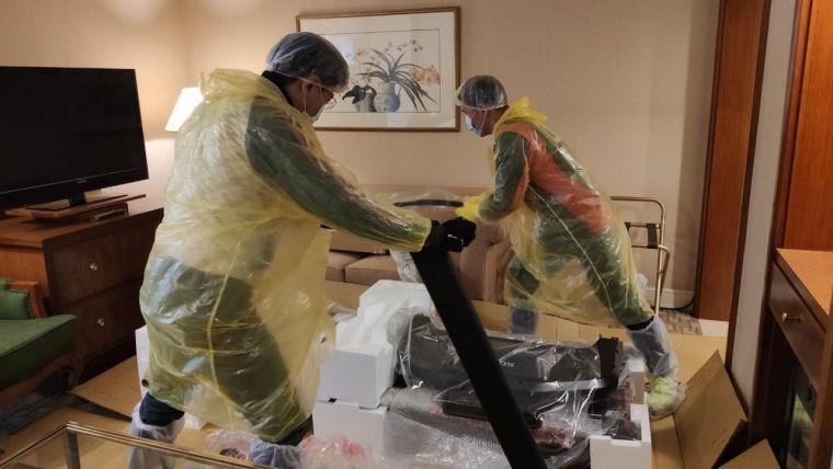 身著全套防護裝備的技師們在隔離客房內安裝跑步機。大會提供