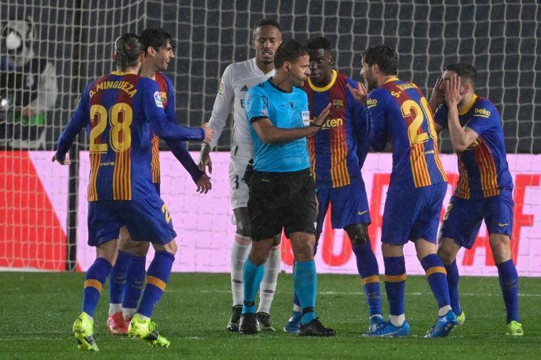 比賽收尾時刻,巴薩眾多球員向主裁判訴求判罰點球。(法新社)