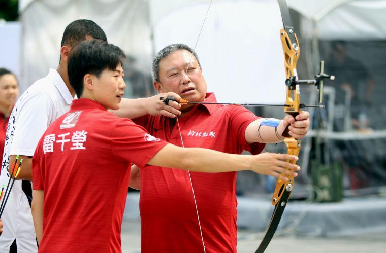 凱撒隊雷千瑩指導中華奧會主席林鴻道射箭。中華企業射箭聯賽聯盟/提供。