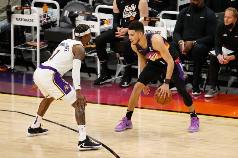 布克(右)季後賽首秀表現出色,34分7籃板8助攻。(法新社)