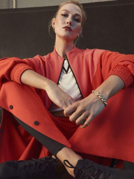 adidas x Karlie Kloss 2021春季聯名系列橘紅短版寬袖外套,採雙面針織、立體布料異材質拼接撞色設計,搭配兩側採用開放式鈕扣設計的橘色寬褲,為造型增添亮點。官方提供
