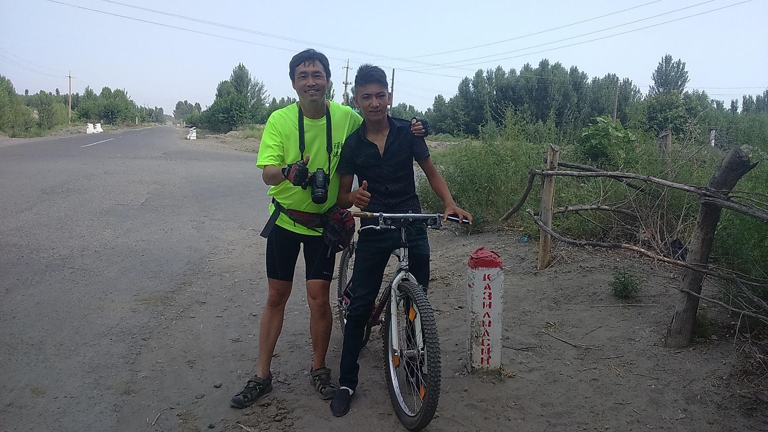 在烏茲別克有當地騎士(右)自動加入陪騎行列,左為陳守忠。單車環球狀遊聯盟提供